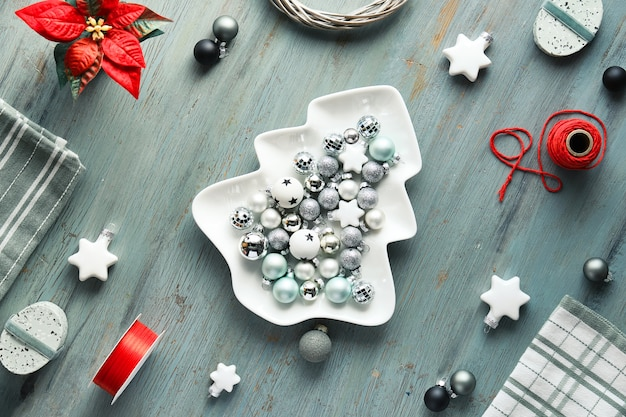 Kerst achtergrond op donkergrijs hout in wit en rood. kerstboomvormig bord met kerstballen, geometrische plat leggen met speelgoed, bloemen, geschenkdozen.