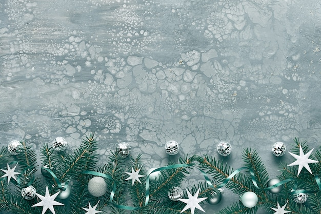Kerst achtergrond, plat lag met spartakjes, spiegel discoballen en zilveren sterren op grijs getextureerd bord, kopie-ruimte