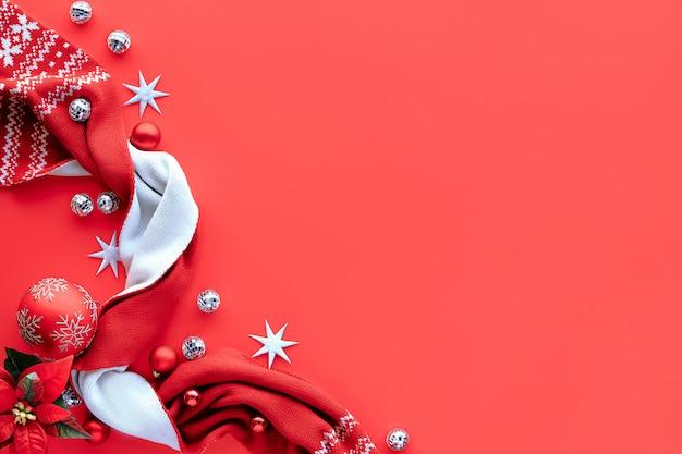 Kerst achtergrond, plat lag met witte en rode versieringen op koraal rode achtergrond, plaats voor tekst. sjaal, discoballen, kerstballen.