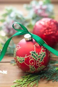 Kerst achtergrond. rode mooie kerstbal met groen lint, dennentakken.