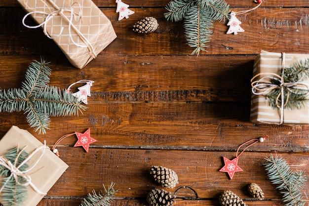 Kerst achtergrond samengesteld uit verpakte geschenkdozen, dennenappels, naaldbomen, decoratieve rode sterren en witte sparren