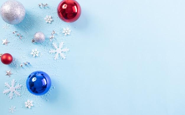 Kerst achtergrond samenstelling. bovenaanzicht van kerstmisbal met sneeuwvlokken op lichtblauwe pastelkleurachtergrond. kopieer ruimte.