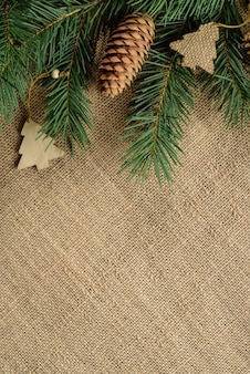 Kerst achtergrond van natuurlijke materialen. decoratieve rand gemaakt van dennentakken en kerstmisspeelgoed op een juteachtergrond.