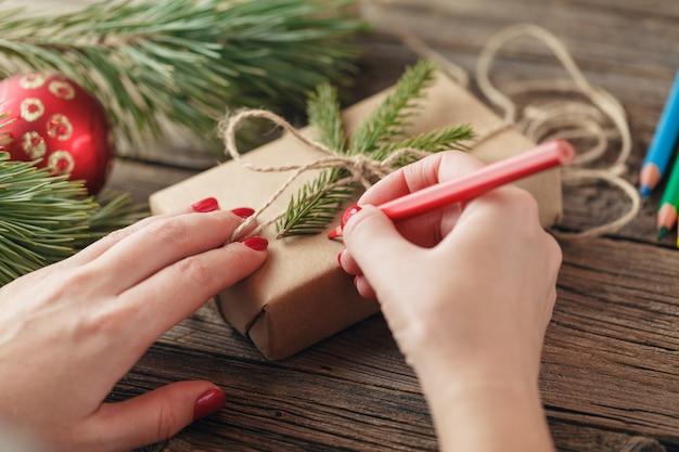 Kerst achtergrond. weergave van handen schrijven op geschenkdoos. verpakte geschenken en rollen, vuren takken op armoedige houten tafel. werkplaats voor het voorbereiden van handgemaakte nieuwjaarsdecoraties.