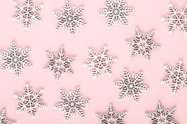 Kerst achtergrond. witte sneeuwversieringen op een roze achtergrond.