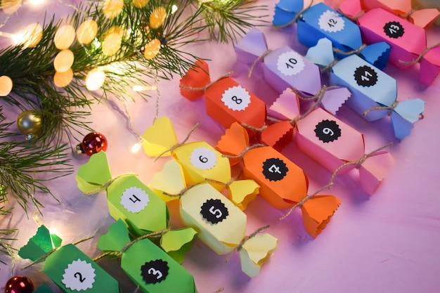 Kerst advent is een kalender gemaakt van gekleurd papier, gemaakt met je eigen handen op een roze achtergrond.