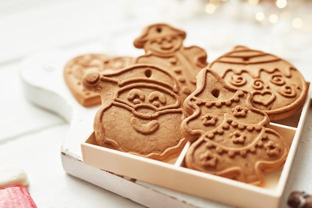 Kerst ansichtkaart template. peperkoekkoekjes op witte lijst. sneeuwvlok, santa, man, snoep vormen. kerstmiskoekjes op witte houten lijst. kerstkoekjes met feestelijke decoratie