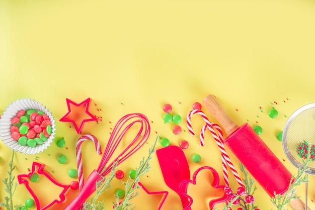 Kerst bakgerei en ingrediënten. banketbakker of baker workplace, met gebruiksvoorwerpen en accessoires voor het maken van feestelijke zoete kerstkoekjes, cakes. helder gele achtergrond kopie ruimte hierboven