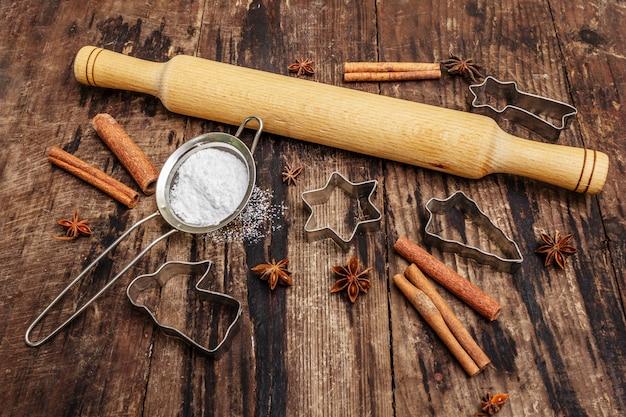 Kerst bakken, bakken, kruiden, koekjessnijders - sterren, engel en dennenboom, zeef, suikerpoeder en een deegroller. oude houten planken