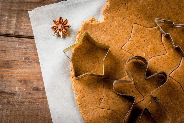 Kerst bakken gemberdeeg voor peperkoek peperkoek mannen sterren kerstbomen deegrol specerijen (kaneel en anijs) bloem op de keuken thuis houten tafel
