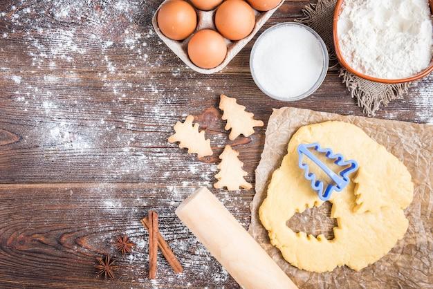 Kerst bakken van gemberkoekjes op donkere houten achtergrond met fir takken.