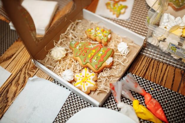 Kerst bakkerij. vrienden versieren van versgebakken peperkoekkoekjes