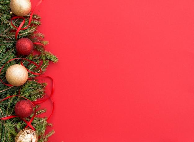 Kerst ballonnen op een rode achtergrond met groene sparren takken en lint