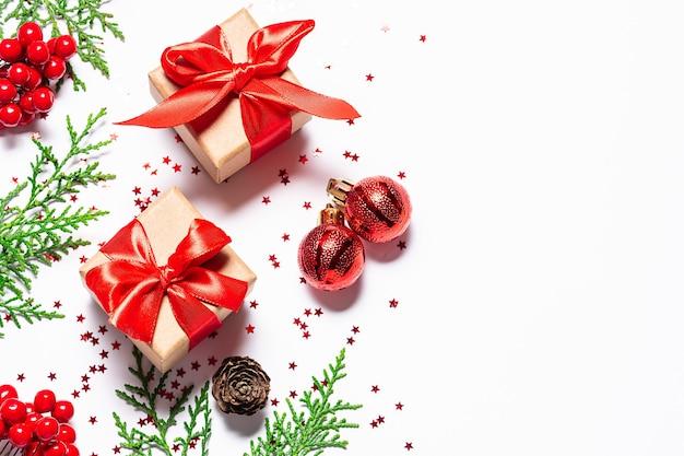 Kerst banner met fir tree takken, geschenkdoos in ambachtelijk papier en rode decoraties op witte achtergrond.