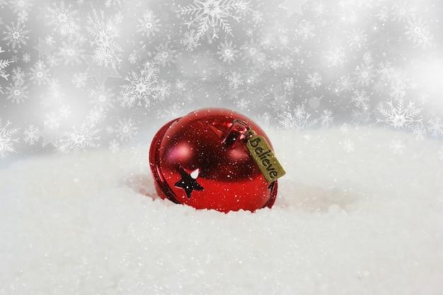 Kerst bel met geloof label genesteld in de sneeuw