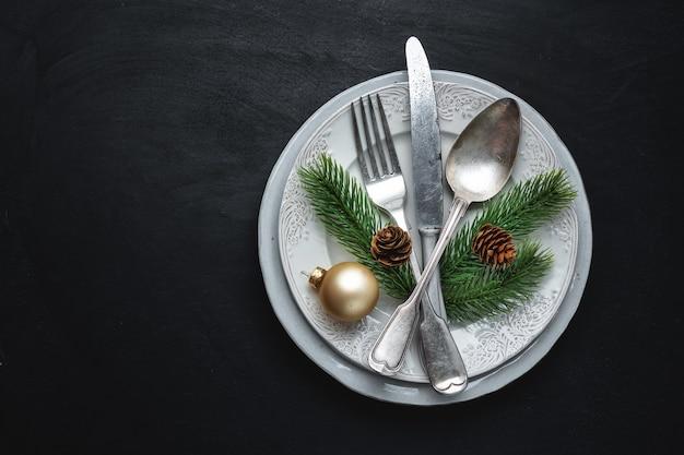 Kerst bestek op plaat met kerst deco op tafel.