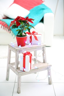 Kerst bloem poinsettia en decoraties op decoratieve ladder met kerstversiering, op lichte achtergrond