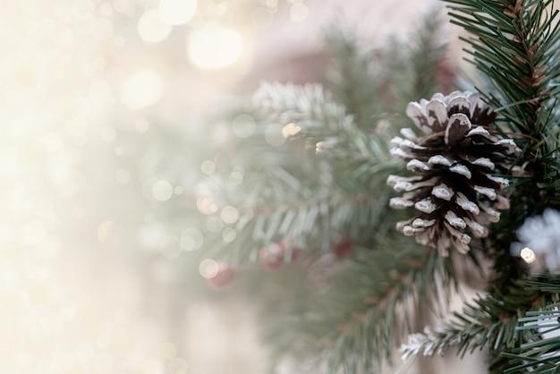 Kerst bokeh effect achtergrond met dennentakken, kegels en ruimte voor inscriptie