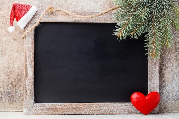 Kerst bord met decoratie. kerstmuts, sterren, houten achtergrond. vintage rustieke stijl.