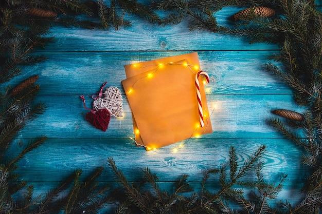 Kerst brief aan de kerstman op een houten blauwe tafel. verlichte krans. bespotten.