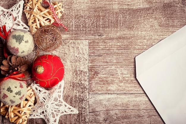 Kerst brief en ornamenten in vintage toning op houten achtergrond. kerstboodschap aan de kerstman