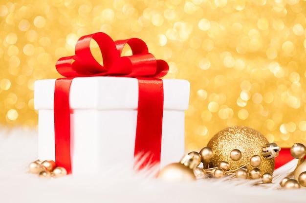Kerst cadeau doos en ornamenten tegen gouden bokeh oppervlak