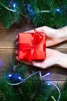 Kerst cadeau vak in vrouwelijke handen op een houten tafel
