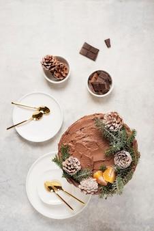 Kerst cake met chocolade versierd met dennenappels en pijnboom op lichte achtergrond