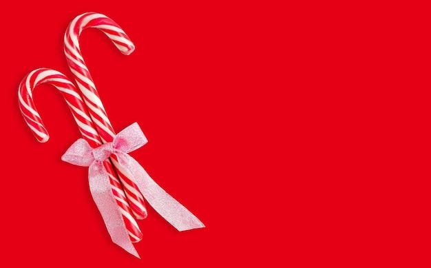 Kerst candy canes met lint geïsoleerd op rode achtergrond met uitknippad