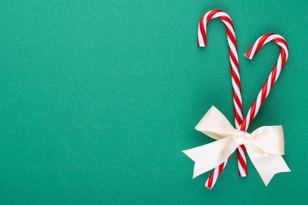 Kerst candy canes, stick en decor op kleur achtergrond. zoete kerstkaart - snoepstokken met lint - afbeelding.