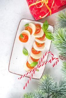 Kerst caprese salade in de vorm van candy cane, mozzarella en tomaten op plaat