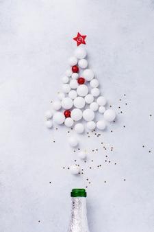 Kerst champagne fles met hagelslag in de vorm van een kerstboom gemaakt van rood en wit speelgoed ballen versierd gouden confetti op wit.