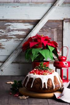 Kerst-chocoladetaart met witte suikerglazuur en granaatappel kernels een houten donker met rode lantaarn en poinsettia