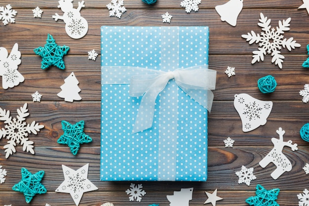 Kerst compositie. geschenkdoos met nieuwjaarsversieringen op gekleurde achtergrond. kerstmis, winter, nieuwjaarsconcept. plat lag, bovenaanzicht, kopieer ruimte.