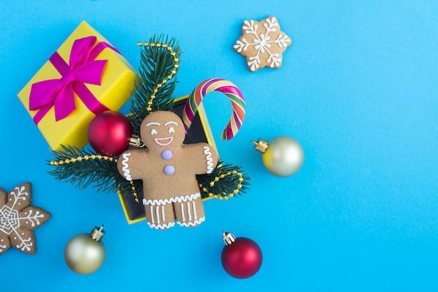 Kerst compositie in een gele geschenkdoos op het blauwe oppervlak.