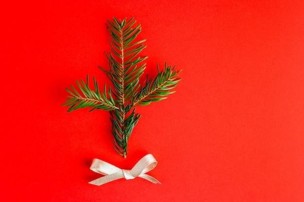 Kerst compositie. kerstboomtak op rode achtergrond. platliggend, bovenaanzicht