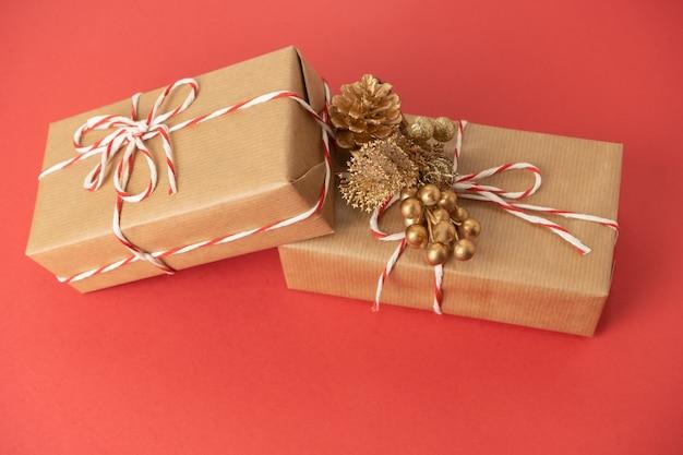 Kerst compositie. kerstcadeaus, gouden versieringen op rode achtergrond.