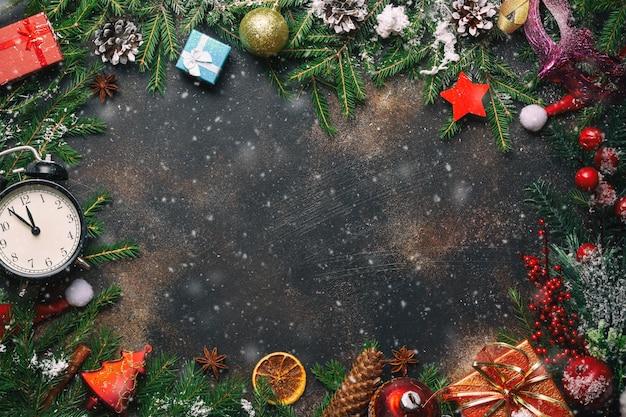 Kerst compositie. kerstcadeaus, pijnboomtakken, speelgoed, vintage klok, anijs sterren, kerstmuts op stenen achtergrond met vrije ruimte en sneeuw. plat lag, bovenaanzicht.