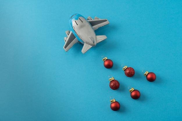 Kerst compositie. kindervliegtuig op een blauwe achtergrond en rode kerstballen