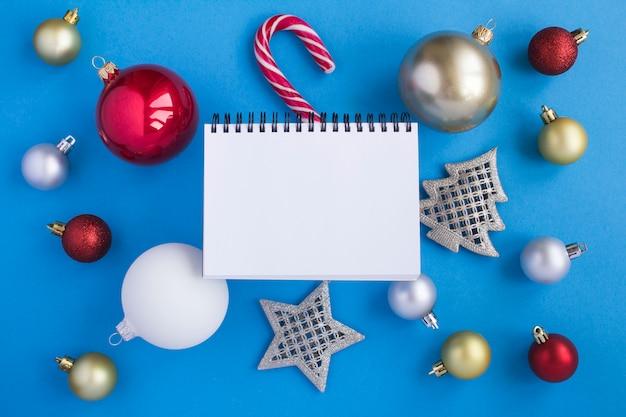 Kerst compositie met open kladblok en kleurrijke ballen op het blauwe oppervlak. kopieer ruimte. bovenaanzicht.