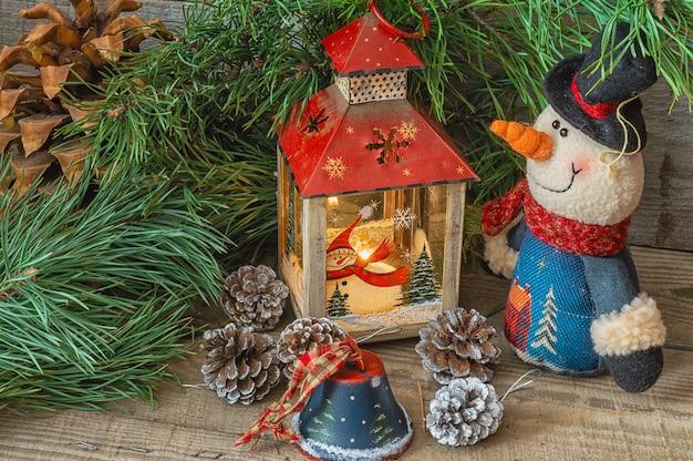 Kerst compositie met sneeuwpop, spar takken, klokken, dennenappels, kerst lantaarn.