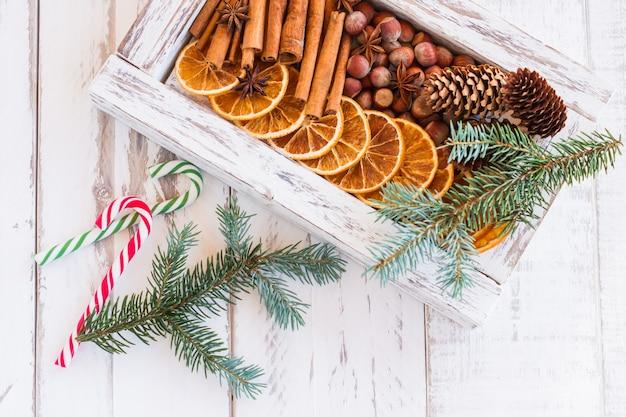 Kerst compositie. regeling van droge sinaasappelen, kaneelstokjes, anijssterren en noten in een doos. bont boomtakken en snoep stokken op houten achtergrond. rustieke ingrediënten voor vakantiekruiden.