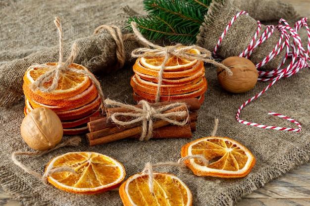 Kerst compositie. regeling van droge sinaasappelen, kaneelstokjes, bontboomtakken en walnoten op houten ondergrond. rustieke ingrediënten voor vakantiekruiden.