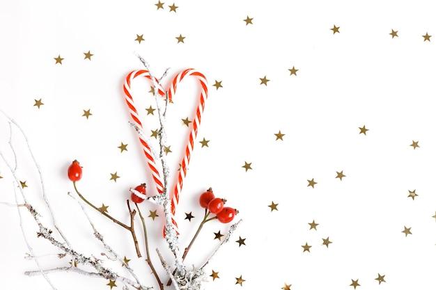 Kerst compositie. rode rozenbottelbessen, kerstsuikergoed op een witte achtergrond en gouden sterren. kerstmis, nieuwjaar, winterconcept. platliggend, bovenaanzicht, kopieerruimte