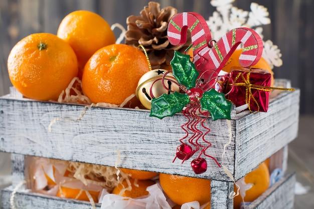Kerst compositie. verse mandarijnen en nieuwjaarsspeelgoed in een doos op het oude houten oppervlak. rustieke stijl. selectieve aandacht.