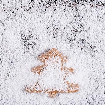 Kerst concept achtergrond, handgemaakte peperkoek in de vorm van een kerstboom op een houten tafel, gefrustreerd door witte sneeuw