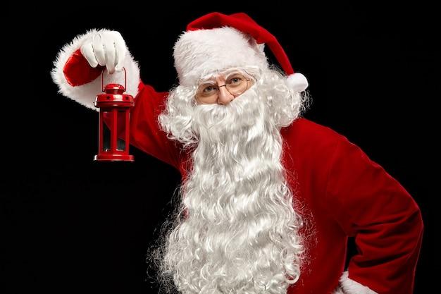 Kerst concept. de kerstman houdt een lantaarn in zijn hand en kijkt in de camera op een zwarte