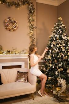 Kerst concept, een meisje in een witte jurk vormt door een kerstboom in een versierd interieur