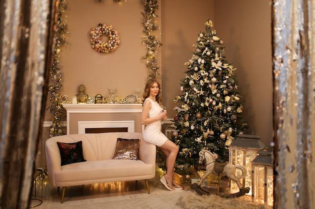 Kerst concept, een meisje met een kapsel in een witte jurk vormt door een boom in een versierd interieur