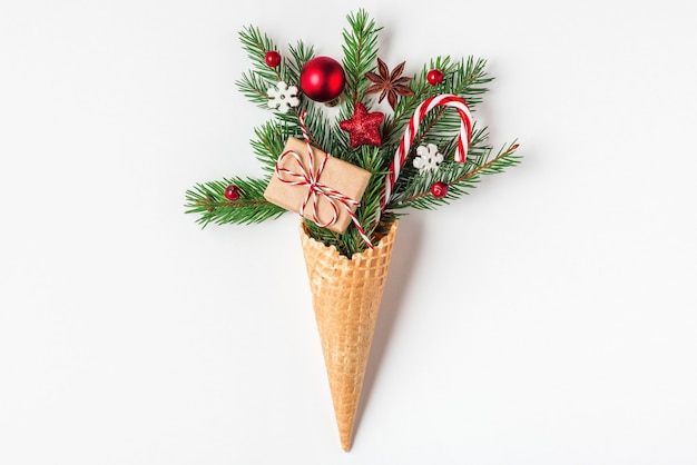Kerst concept. fir tree takken, geschenkdoos en kerstversiering in wafel-ijsje op witte achtergrond. bovenaanzicht. plat leggen